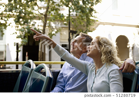 A middle-aged couple sitting on a sightseeing bus, admiring the view 51280719
