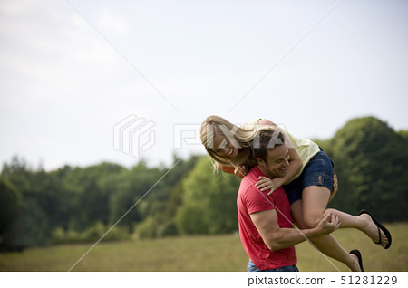 A young couple lifting his girlfriend in a field in summertime 51281229