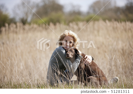 A mature woman sitting on the grass hugging her dog 51281311