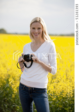 A young woman standing next to a rape seed field in flower, holding a camera 51281393