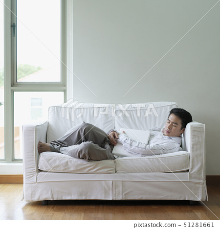 Side profile of a young man sleeping on a couch 51281661