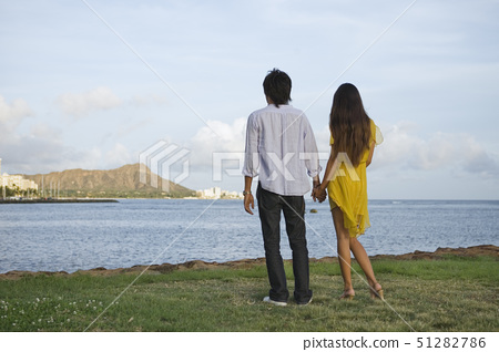 Rear view of a young couple holding hands 51282786