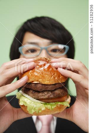 Young man holding burger 51282936