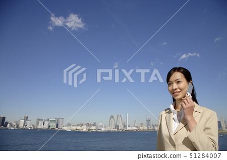 Japan, Honshu, Tokyo, Young businesswoman using mobile phone, smiling 51284007