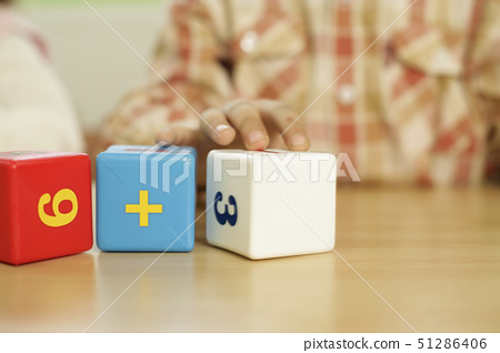 Child playing with building blocks with numbers 51286406