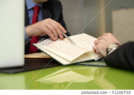 Two businessmen at desktop with a book 51286738