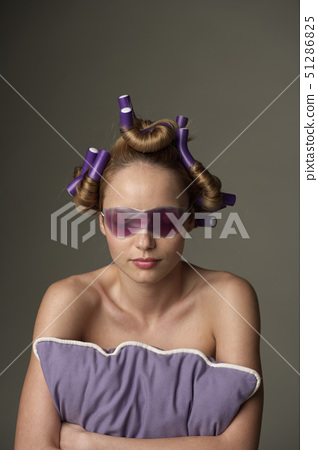 Young woman wearing eye mask and curlers 51286825