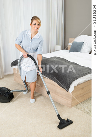Housekeeper Cleaning With Vacuum Cleaner 51316204