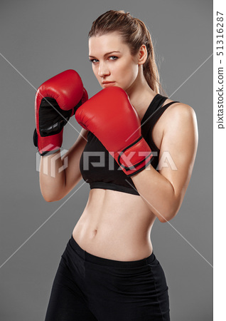 beautiful woman is boxing on gray background 51316287