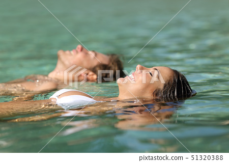 Couple of tourists swimming in the sea of a tropical resort 51320388