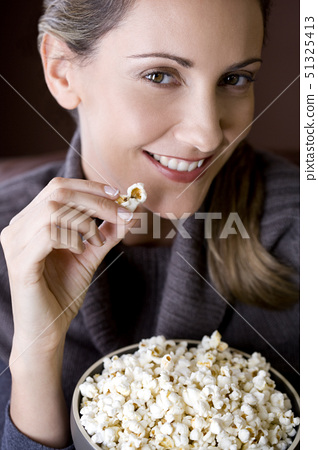 A mid adult woman eating popcorn 51325413