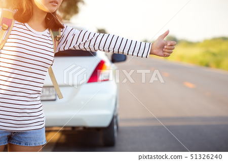 woman hitchhiking looking for help with her broken car on the road 51326240