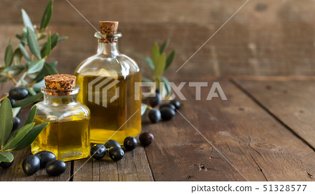 Olive oil and fresh olives on wood background 51328577