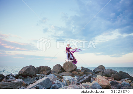 Young romantic woman posing on the beach watching the sunset 51328870
