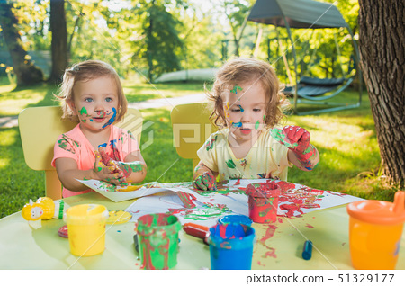 Two-year old girls painting with poster paintings together against green lawn 51329177