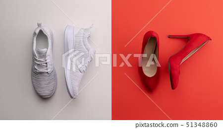 A studio shot of pair of running vs high heel shoes on color background. Flat lay. 51348860