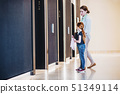 A side view of businesswoman with small daughter in office building. 51349114