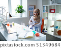 Female chemist wearing hijab feeling tired after samples analysis 51349684