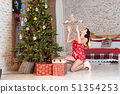 Beautiful young woman playing with a teddy bear by the Christmas tree 51354253