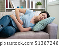 japanese woman with stomach ache lying on sofa 51387248