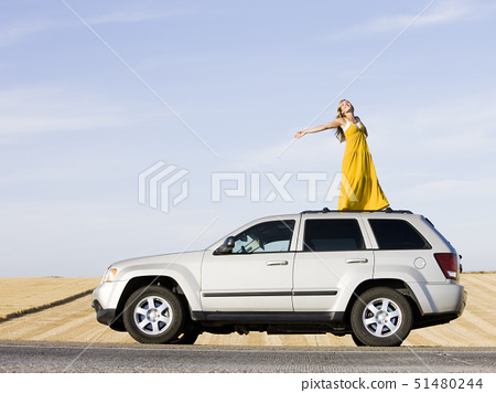 woman standing on the roof of her car on the side of the road 51480244