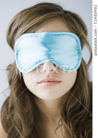 young woman wearing a sleeping mask 51480492