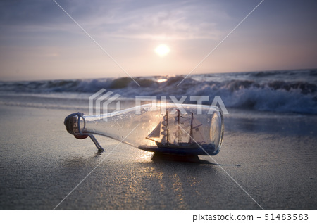 Ship in bottle on beach 51483583