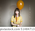 Studio shot of woman with balloon and party blower 51484713