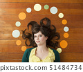 Portrait of young woman against wooden background with decoration 51484734