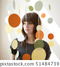 Portrait of young woman under hanging decoration 51484739