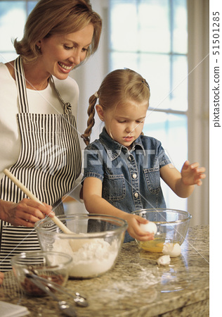 Mother and daughter baking together 51501285