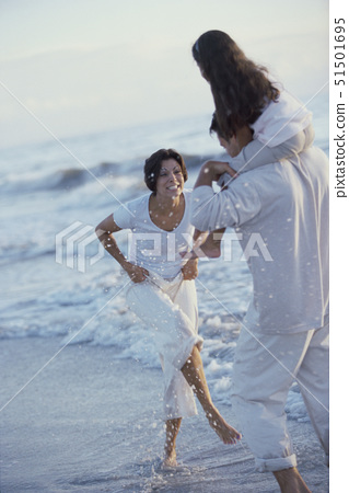 Father and mother together with their daughter at the beach 51501695