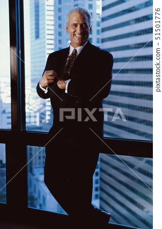 Portrait of a businessman standing against a window 51501776