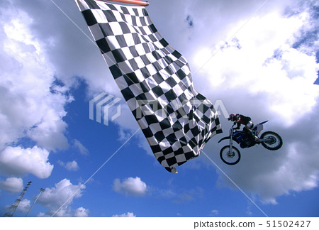 Low angle view of a man performing stunts on a motorcycle 51502427