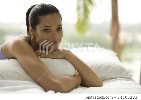 Portrait of a young woman lying on a bed 51503223