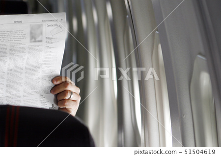 Man reading a newspaper in an airplane 51504619