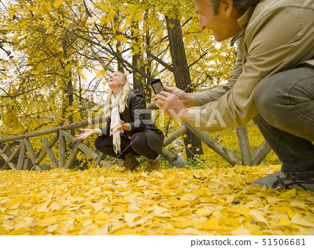 Italy, Piedmont, Couple taking pictures of autumn leaves 51506681