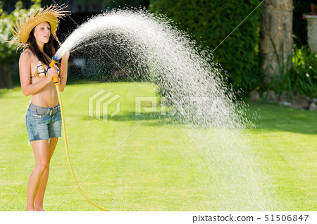 Summer garden grass woman play with water hose sunny day 51506847