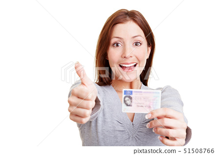 Happy woman with European driving license holding her thumbs up 51508766
