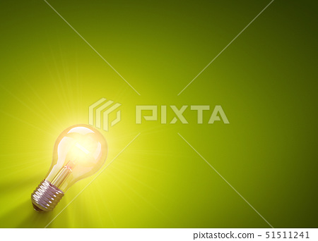 A lightbulb positioned in the bottom left corner laying down & illuminating a green surface. Gener 51511241