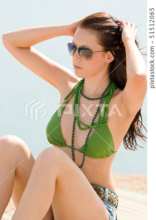 Summer beach young woman sunbathing in bikini alone 51512065
