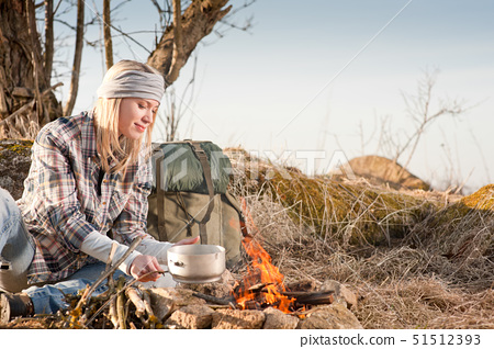 Young hiking woman with backpack cook on campfire in countryside 51512393