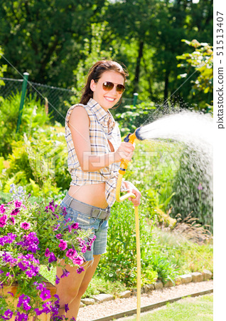 Summer garden smiling woman watering hose flower sunny day 51513407