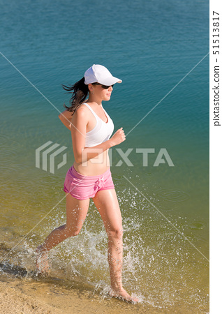 Summer active woman jogging on beach seashore in fitness outfit 51513817