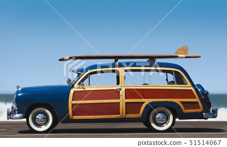side view of woody car with surfboard and surf in background 51514067