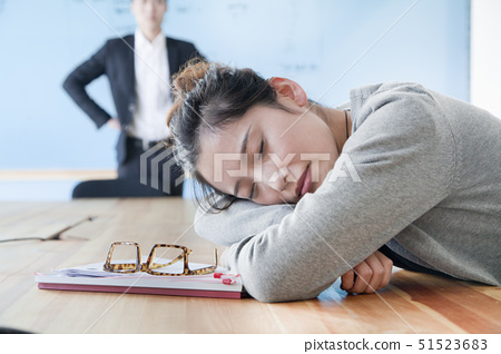Young businesswoman sleeping during meeting, disappointed Boss looking at her 51523683