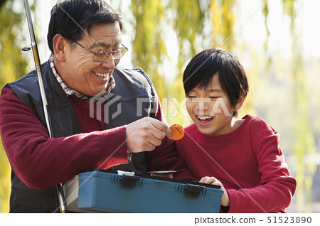 Grandfather and grandson looking at fishing tackle box 51523890