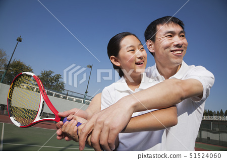 Young girl playing tennis with her coach 51524060