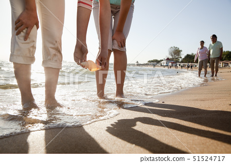 Mother and daughter picking up a shell on the beach 51524717