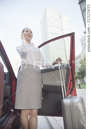 Young Businesswoman outside of her car talking on the phone 51525655